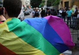 Un activista luce una bandera con los colores que identifican la causa homosexual en el mundo. (Foto Prensa Libre: AP).