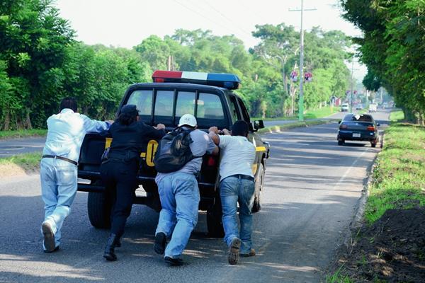 Tres vecinos ayudan a los agentes policiales a empujar el autopatrulla, el cual no podían movilizar por problemas mecánicos, en la cabecera de Retalhuleu. (Foto Prensa Libre: Jorge Tizol)