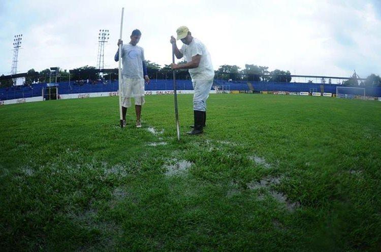 Trabajadores del estadio trabajan para sacar el agua del terreno de juego.
