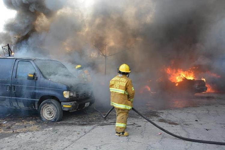 Bombero sofoca las llamas del incendio que causó daños en un predio de la PNC. (Foto Prensa Libre: Carlos Enrique Paredes)