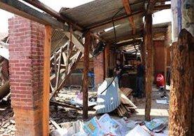 Dos personas observan parte de los escombros que quedaron en el mercado de Santa Cruz del Quiché. (Foto Prensa Libre: Héctor Cordero).