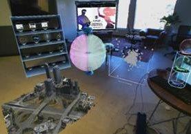 El sistema superpone hologramas en una oficina real, permitiendo manipular elementos con las manos. (METAVISION.COM)