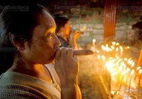 """Una mujer fuma un puro en el rito conocido como """"la limpia"""". (Foto: Carlos Sebastián)"""