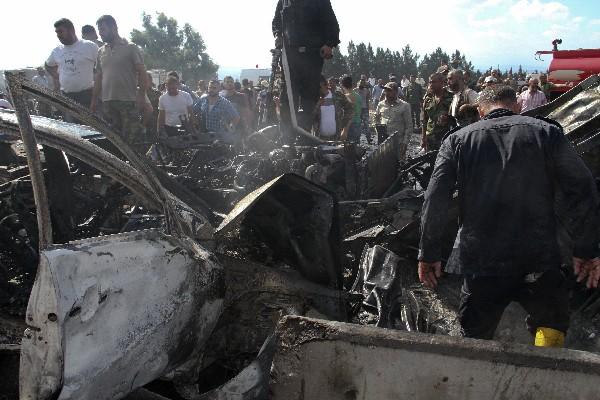 Servicios de emergencia y residente ven los restos de vehículos quemados en Tartus, Siria.(AP).