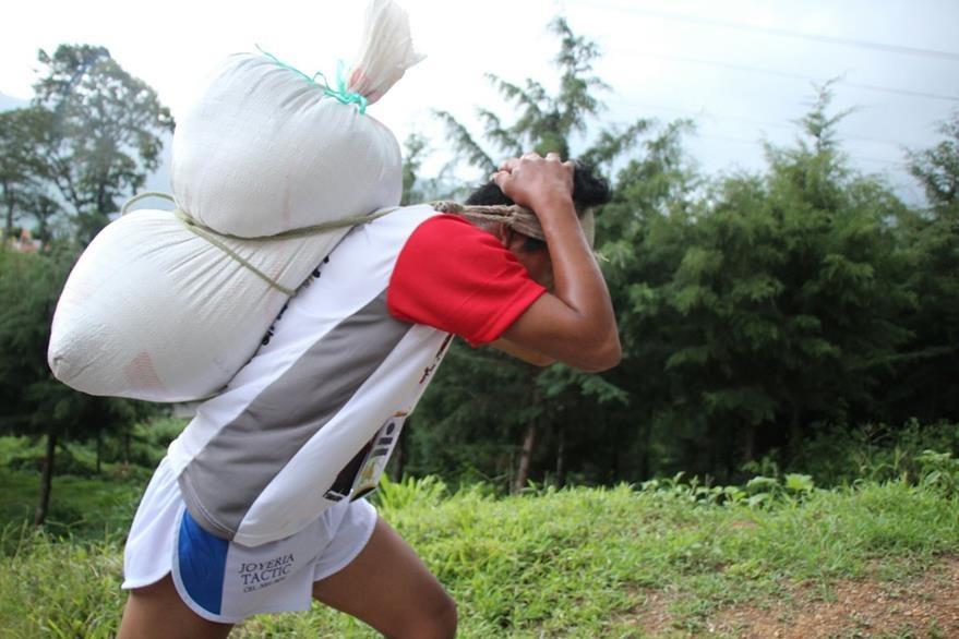 Cada uno de los competidores carga un saco de maíz, con el cual deben llegar a la meta, en el área central de Tactic, Alta Verapaz. (Foto Prensa Libre: Eduardo Sam Chun)