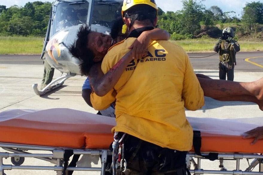 Un oficial de las Fuerzas Aéreas de Combate carga a la mujer hacia la aeronave después que la pusieron a salvo. (Foto Prensa Libre: AFP).