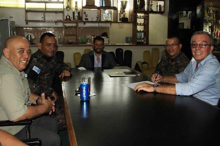 El presidente de Aurora, Carlos Castro junto a otros integrantes de la directiva militar, firman el contrato con el técnico Ariel Sena.