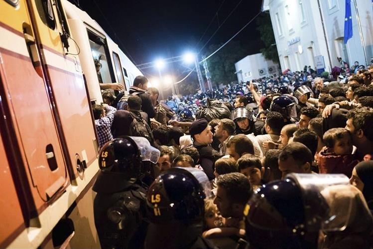 <em>Refugiados intentan subir a un tren en la frontera entre Serbia y Croacia.</em>