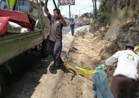 Trabajadores de la Municipalidad de Mixco recogen piezas del tráiler que se accidentó en el kilómetro 18.5 de la ruta Interamericana. (Foto Prensa Libre: Esbin García)