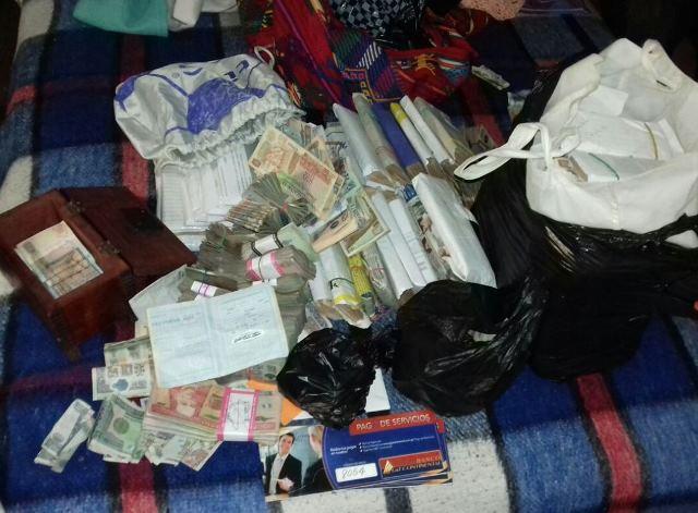 En vivienda usada como buzón —guarida donde ocultan dinero y armas— se encontró  más de Q1 millón. (Foto Prensa Libre: PNC)