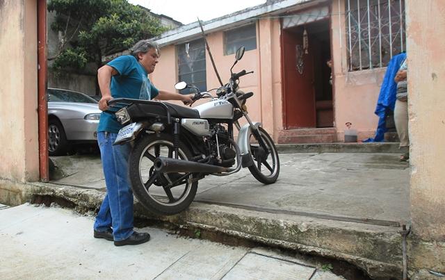 Héctor Madrid regresó a su trabajo inicial, el de reparar motocicletas, ya que no puede ingresar vehículos al patio de su casa, donde funciona su taller de mecánica. (Foto Prensa Libre: Esbin García)
