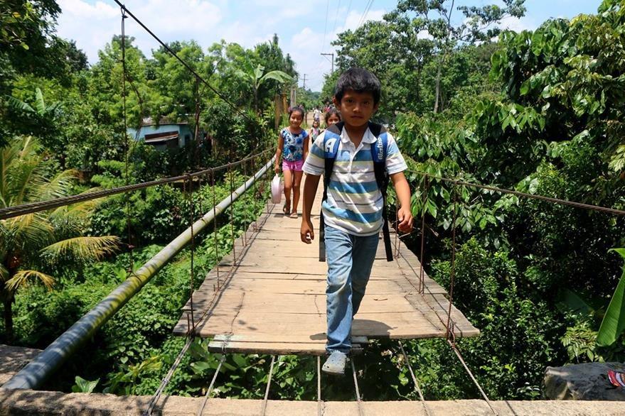 Niños cruzan un puente colgante dañado para llegar a su establecimiento educativo en  El Esfuerzo, San Felipe, Retalhuleu. (Foto Prensa Libre: Rolando Miranda)