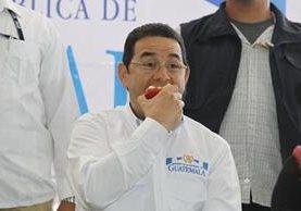 Jimmy Morales degusta la manzana que le regalaron vendedores de La Terminal. (Foto Prensa Libre: Paulo Raquec)