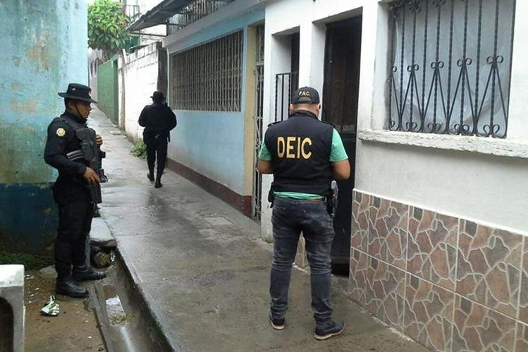 Agentes de la PNC resguardan viviendas allanadas en Zacapa e Izabal, en busca de presuntos integrantes de una banda delincuencial. (Foto Prensa Libre: PNC)