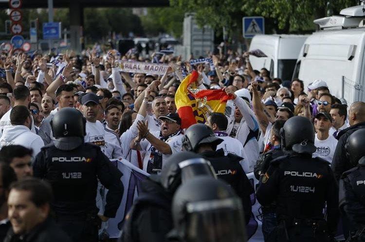 Los aficionados del Real Madrid son resguardados por la seguridad antes de ingresar al estadio.