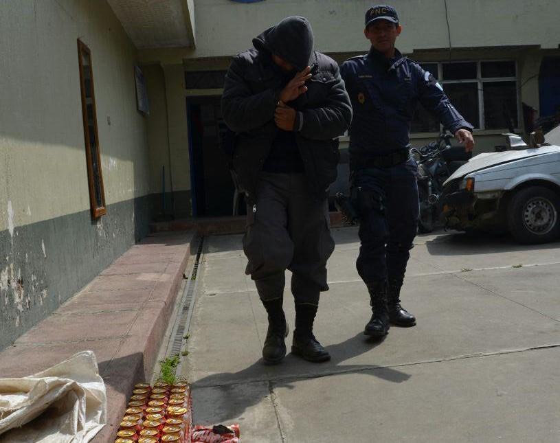 El policía capturado junto a lo decomisado, en Cantel. (Foto Prensa Libre: María José Longo).