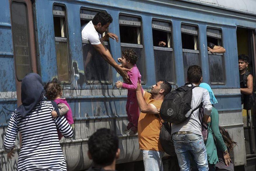 Un hombre trata de subir a un tren por la ventana a una nena. Miles sueñan con llegar a los países industrializados de Europa. (Foto Prensa Libre: EFE).