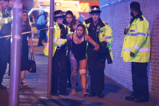 Una joven herida sale escoltada por varios agentes de policía minutos después del ataque al Manchester Arena. JOEL GOODMAN/LNP