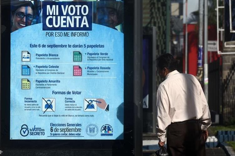 A man looks at a poster of the Supreme Electoral Tribunal which invites the population to vote, in Guatemala City on September 5, 2015 on the eve of Guatemala
