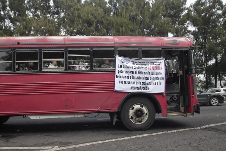 Buses de transporte urbano circulan con mantas en las que se exige el pago del subsidio de parte del Gobierno. (Foto Prensa Libre: Hemeroteca PL)