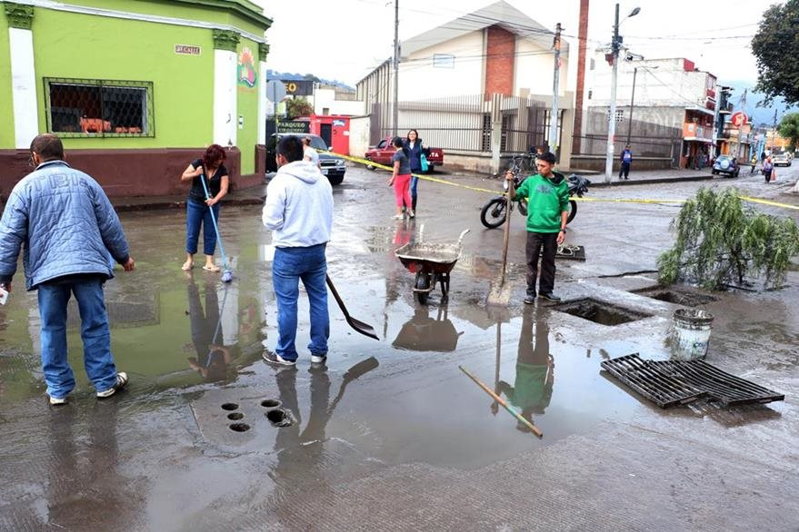Comerciantes y vecinos retiran lodo arrastrado por correntadas en un sector de Xela. (Foto Prensa Libre: Carlos Ventura)