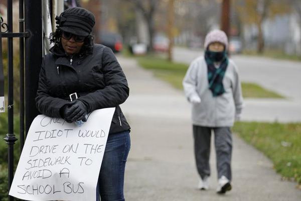 """<p>Mujer sostiene cartel que dice """"Solo un idiota conduce sobre la acera para rebasar a un autobús escolar. (Foto Prensa Libre: AP)</p>"""