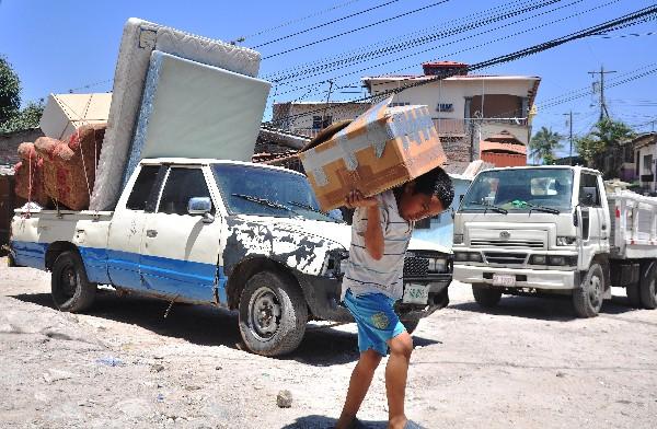 Un niño carga pertenencias en un barrio de Tegucigalpa, Honduras.