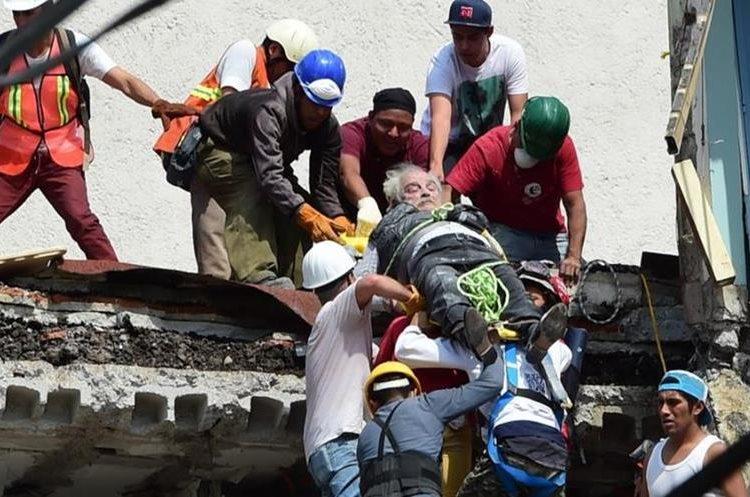 Varias personas colaboran en el rescate de un anciano en una de la zonas afectadas. (Foto Prensa Libre: Agencias)
