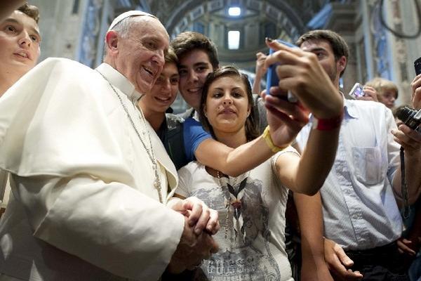 El Papa Francisco acepta tomarse un selfie con un grupo de adolescentes.