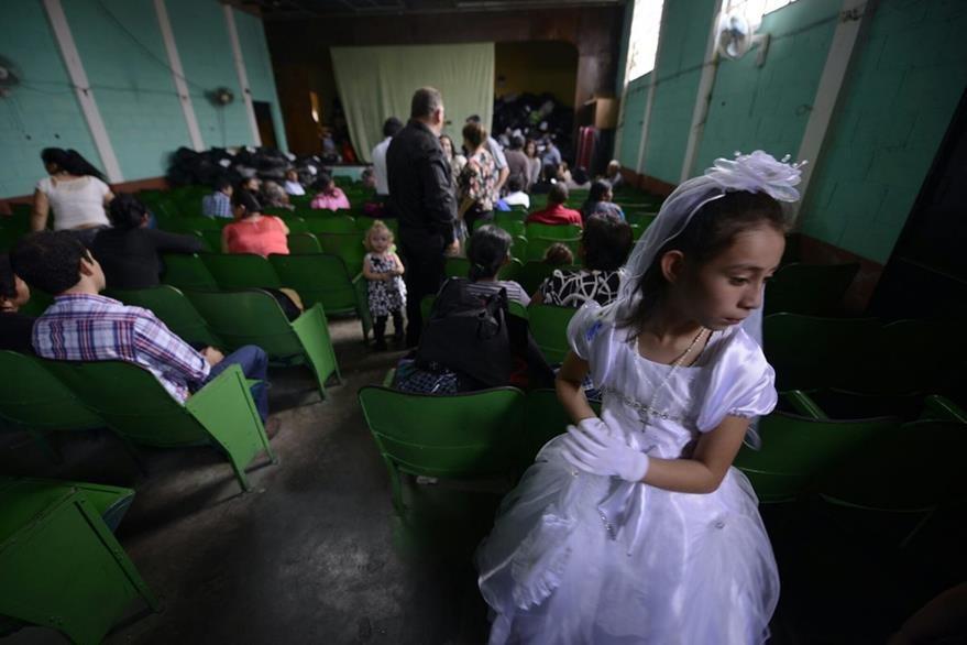 Una niña permanece en una bodega de Santa Catarina Pinula después de realizar su primera comunión. (Foto Prensa Libre: Agencia EFE)