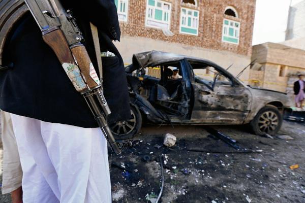 Un integrante de la milicia hutí permanece junto aun vehículo destrozado por el atentado. (Foto Prensa Libre:EFE)