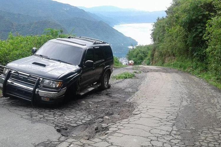 Grandes agujeros complican el tránsito hacia cinco municipios de la cuenca del Lago de Atitlán, Sololá, (Foto Prensa Libre: Ángel Julajuj)
