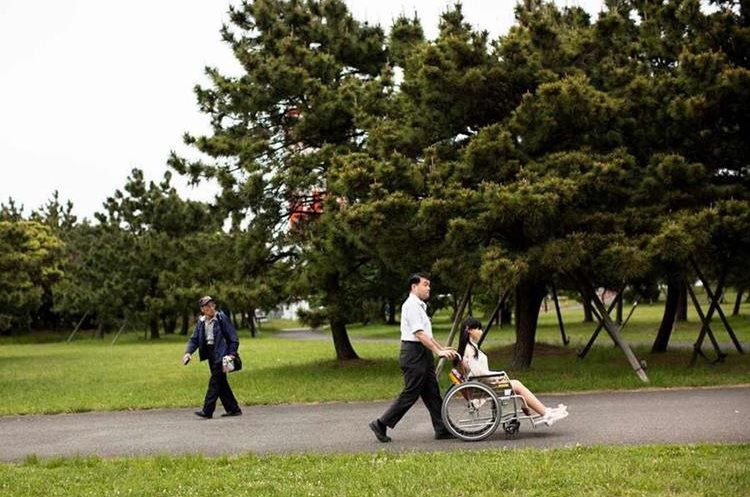 Masayuki Ozaki pasea a Mayu en una silla de ruedas.