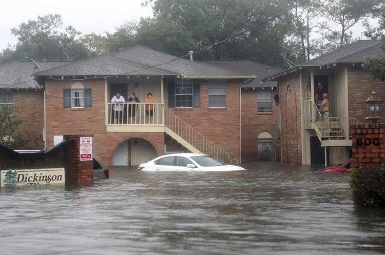 Una familia espera ayuda en el segundo piso de un complejo de apartamentos en Dickinson, Texas.(AP).