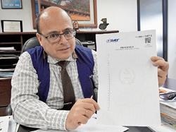 abel cruz, intendente de Recaudación, muestra las nuevas hojas de papel protocolo.