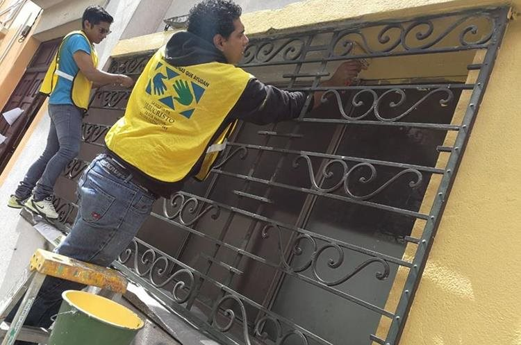 Jóvenes mormones pintan casas de la  Sexta Avenida. (Foto Prensa Libre: Óscar Rivas)