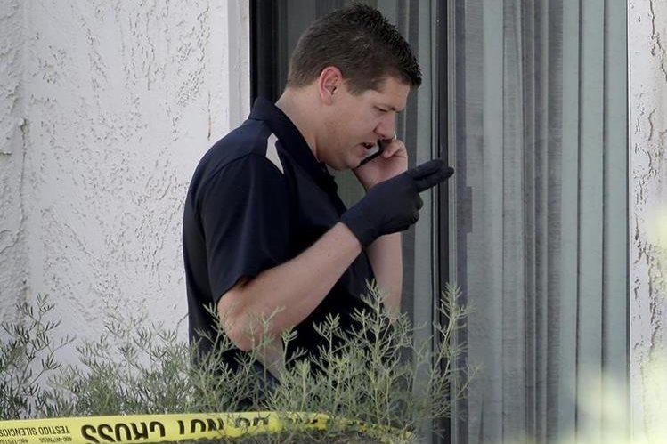 Un oficial de la Policía de Phoenix, durante una diligencia en la vivienda donde ocurrió el macabro crimen. (Foto Prensa Libre: AP).
