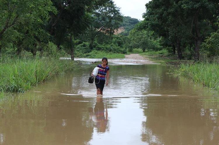 Una vecina del barrio Tikal, San Benito, cruza una de las calles anegadas por las lluvias. (Foto Prensa Libre: Rigoberto Escobar)