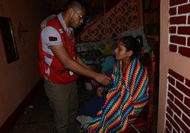 María Méndez, madre de la menor que muró carbonizada, luce desconsolada mientras un socorrista de Cruz Roja la revisa. (Foto Prensa Libre: María José Longo)