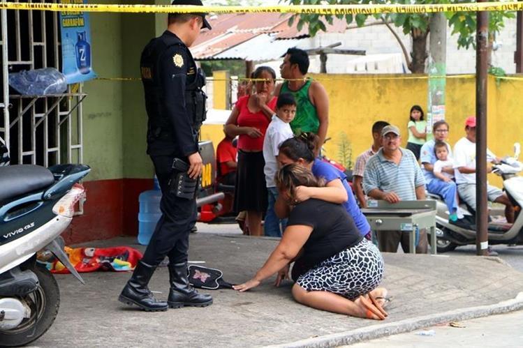 La madre del niño y otros familiares lloran junto al cuerpo del bebé el día que fue arrollado y murió. (Foto Prensa Libre: Rolando Miranda)