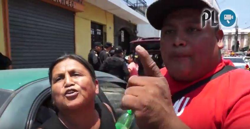 El sujeto de camisa roja golpea dos veces la cámara de la reportera, la intimida junto a la mujer de traje negro. (Foto Prensa Libre)