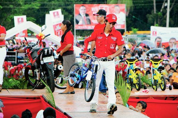 Un animador del partido Líder lleva una bicicleta que regalaron en el mitin en Caballo Blanco, Retalhuleu. (Foto Prensa Libre: Rolando Miranda)