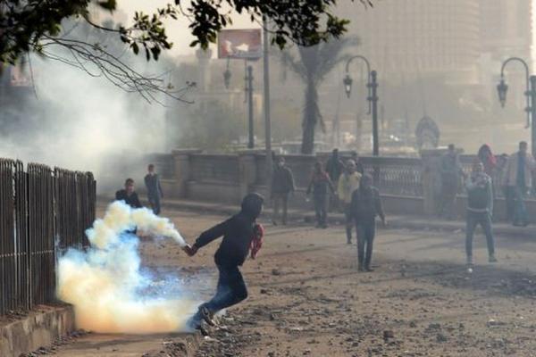<p>Un egipcio se dispone a devolver un cartucho de gas lacrimógeno lanzado por la Policía. (AFP).<br></p>