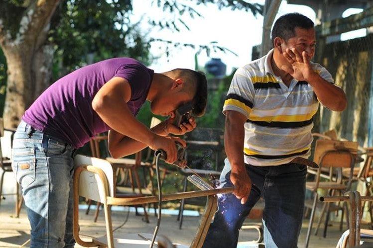 Estudiantes y maestros del Instituto Nacional de Educación Básica, del área urbana de Sayaxché, restauran los pupitres. (Foto Prensa Libre: Rigoberto Escobar)