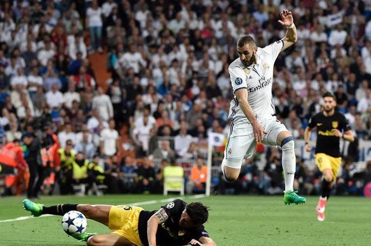 Stefan Savic se barre bien a la pelota frente al francés Karim Benzema que salta para evitar el contacto.