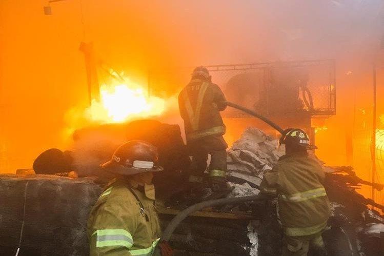 Bomberos Voluntarios combaten las llamas en el interior de la bodega de calzado, en la zona 12. (Foto Prensa Libre: CVB)