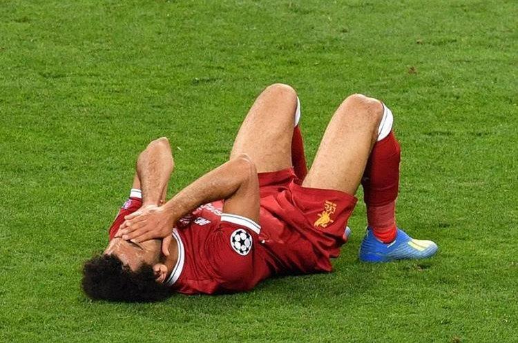Mohamed Salah terminó tendido en el suelo después de resentirse del hombro por un golpe en una jugada con Sergio Ramos. (Foto Prensa Libre: AFP)