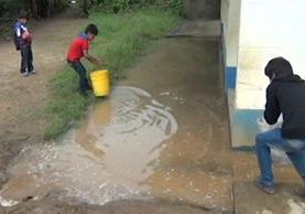 Un estudiante ayuda a sacar el agua reposada en la escuela del caserío Ixquihuilá, San Marcos. (Foto Prensa Libre: Whitmer Barrera)