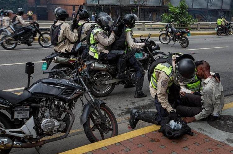 Guardia Nacional Bolivariana trata de auxiliar a un manifestante en Caracas.