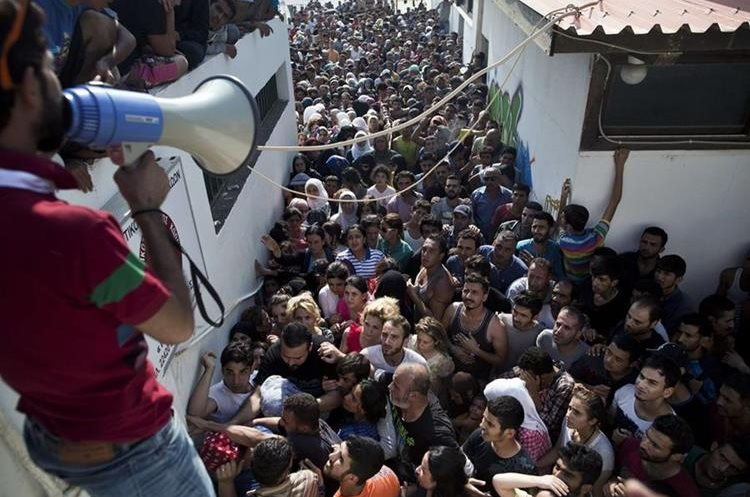 Migrants wait for a registration procedure at the stadium on the Greek island of Kos, on August 11, 2015.  Police on the Greek island on Kos hit migrants with truncheons to prevent a stampede, a day after an officer was caught on camera slapping a migrant. The incident occurred as hundreds of migrants were being relocated to a local football stadium, after camping alongside roads and beaches across the island for weeks. AFP PHOTO / ANGELOS TZORTZINIS